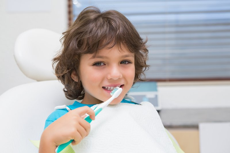 child brushing teeth in dentist chair