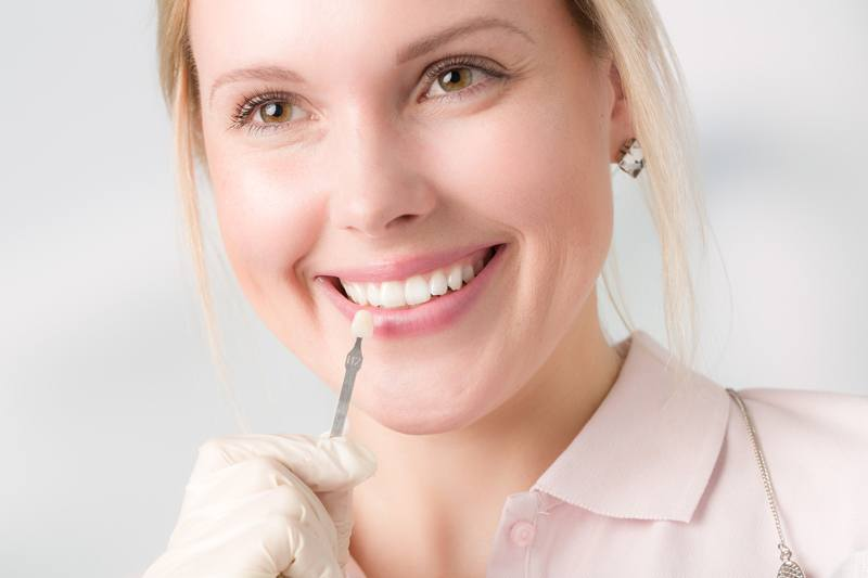 girl holding a dental veneer